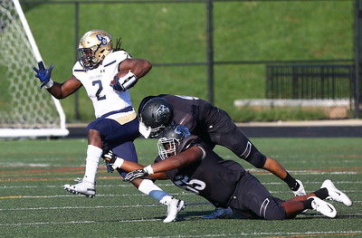 George P. Smith/The Montgomery Sentinel    Our Lady of Good Counsel High School running back Latrele Palmer (2) high steps out of this tackle and takes it for one of the Falcons' touchdowns in the game played at Gaithersburg High School on Saturday, September 29, 2018 due to wet field conditions at Northwest.