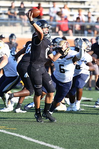 George P. Smith/The Montgomery Sentinel    Northwest High School quarterback Jack Anders (8) throws under pressure from Our Lady of Good Counsel High School'sJulio Ayamel (6) in the game played at Gaithersburg High School on Saturday, September 29, 2018 due to wet field conditions at Northwest.