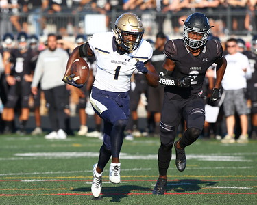 George P. Smith/The Montgomery Sentinel    Our Lady of Good Counsel High School's Cameron Hart (1) runs away from Northwest High School's Andrew Howard (2) for another Good Counsel touchdown (28-0) in the game played at Gaithersburg High School on Saturday, September 29, 2018 due to wet field conditions at Northwest.