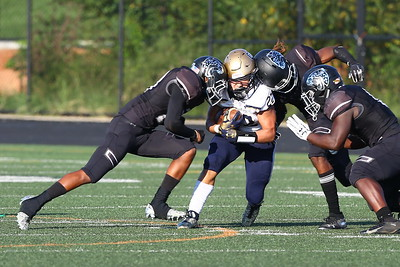 George P. Smith/The Montgomery Sentinel    Our Lady of Good Counsel High School's Jackson Stefanelli (22) got caught between two Northwest High School tacklers in the game played at Gaithersburg High School on Saturday, September 29, 2018 due to wet field conditions at Northwest.