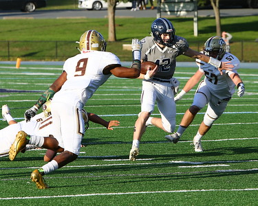 George P. Smith/The Montgomery Sentinel    Georgetown Prep's Peter Davin (12) gains yards with his legs after being flushed out of the pocket.
