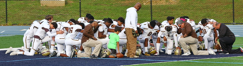 George P. Smith/The Montgomery Sentinel    Landon players and coaches kneel in prayer before the game at Georgetown Prep on Saturday, October 20, 2018.