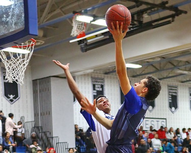 George P. Smith/The Montgomery Sentinel    Springbrook's Marcus Davis (5) taking it to the hoop over Blake's David Hill (11).