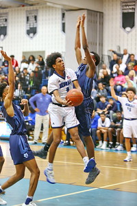 George P. Smith/The Montgomery Sentinel    Blake's Ezana Fekere (0) taking it to the hoop past Springbrook's Jonathan Lapierre (15) and Brian Ayafor (52).