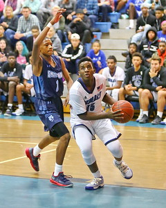 George P. Smith/The Montgomery Sentinel    Blake's Romelle Williams (15) taking it to the hoop past Springbrook's Amare Curtis (1).