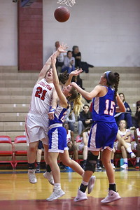 George P. Smith/The Montgomery Sentinel    Wootton's Crystal Bridge (21) powers her way to the hoop past Sherwoo'd Caroline Bidwick (2) and Maddie Tringone (15).