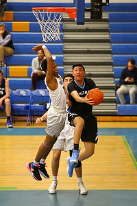George P. Smith/The Montgomery Sentinel    Whitman's Justin Cheng (10) with the baseline reverse layup as Churchill's Ike Onu-Chiedo (20) cranks up to lower the boom.