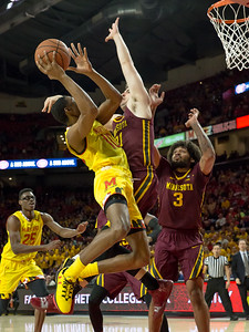 Maryland's Serrel Smith Jr. (10) drives the lane but encounters Minnesota's Brock Stull (31). PHOTO BY MIKE CLARK