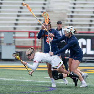 Caroline Steele of Maryland is on the receiving end of this hard check by Syracuse Defensemen Kerry Defliese. PHOTO BY MIKE CLARK