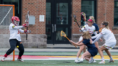 Despite being taken down by the Maryland Defenders, Syracuse's Meaghan Tyrrell (18) manages to score against the Terps Megan Taylor (34). PHOTO BY MIKE CLARK