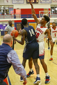 George P. Smith/The Montgomery Sentinel    Thomas Johnson's head coach, Ian Fisher, is practically on the court as Magruder's Ebby Asamoah (14) get trapped next to the sideline by Emmanuel Powe (10).