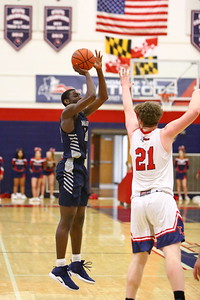 George P. Smith/The Montgomery Sentinel    Magruder's Ebby Asamoah (14) shooting a three over Thomas Johnson's Bennett Commander (21).