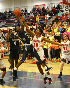 George P. Smith/The Montgomery Sentinel    Magruder's Malik Abudu (32) outhustles a rebound away from Thomas Johnson's Emmanuel Powe (10) early in the Regional Final game.