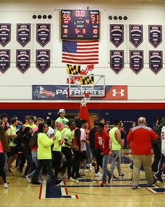 George P. Smith/The Montgomery Sentinel    Thomas Johnson fans storm the court as the Patriots defeat Magruder by a score of 55 to 51 in the Regional Final to advance in the playoffs.