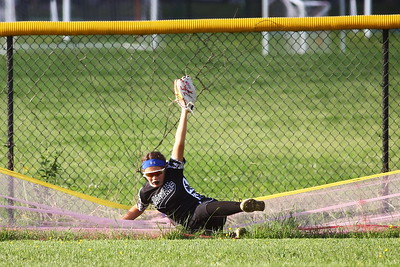 George P. Smith/The Montgomery Sentinel    Northwest outfielder Shawnee Ronyak (6) makes a good catch in-bounds and holds on to the ball as she loses her balance and falls into the safety fence.