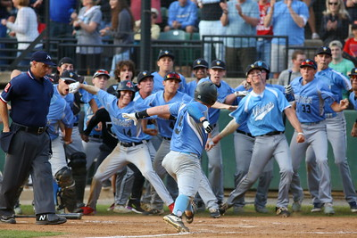 George P. Smith/The Montgomery Sentinel    Walt Whitman's Jack Ryan (9) signals KABOOM as he approaches home plate to a throng of waiting teammates after hitting a home run against Old Mill in the 3rd inning.