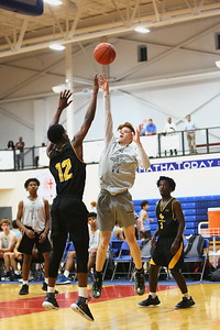 George P. Smith/The Montgomery Sentinel    Richard Montgomery's Ryan Cornish with a runner for 2 over Gwyn Park's Darius Joyner (12). Cornish was 3-8 beyond the arc and 9-17 inside the arc for 28 game points - the high scorer  for RM and the game.
