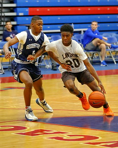 George P. Smith/The Montgomery Sentinel    Landon's Kino Lilly (20) driving the lane past Georgetown Prep's Trevon Marshall (5).