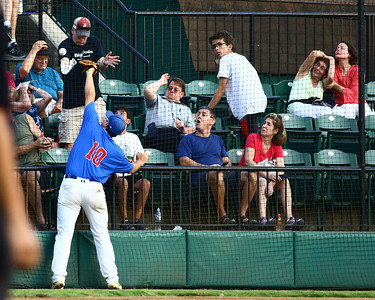George P. Smith/The Montgomery Sentinel    One fan tries to catch the foul ball with his program, others duck for cover, but Silver Spring-Takoma's Lucas Donlon (10) can't save them cause the ball fell on the far side of the net.