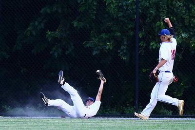George P. Smith/The Montgomery Sentinel    Silver Spring-Takoma's Cole Friese (16) creates a cloud of dust as he slides through the warning track after making a diving catch. Friese held the ball aloft for the ref to see as Lyle Miller-Green (28) gives a celebratory fist pump.