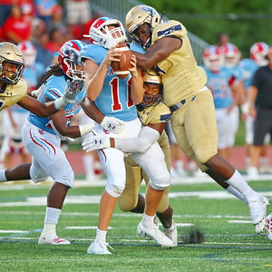 George P. Smith/The Montgomery Sentinel    Good Counsel's DE Kristopher Jenkins (18) and linebacker Harold Miles (4) converge on Charlotte Catholic quarterback Jake Smith (11).