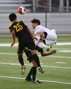 George P. Smith/The Montgomery Sentinel    Gaithersburg's Kevin Calderon (13) falls on Richard Montgomery's Arsenio Paiz (23) after heading the ball.