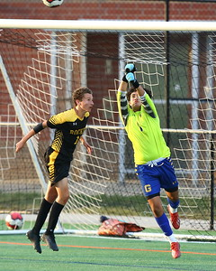 George P. Smith/The Montgomery Sentinel    Gaithersburg's goalie Jonathan Lovo (1) punches the ball out of the goal to keep Richard Montgomery's Joshua Coster 914) from taking a header in front of the net.