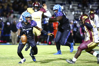 George P. Smith/The Montgomery Sentinel    Blake's quarterback Isaiah Smith (1) gets flushed out of the pocket by Paint Branch's Sulayman Jalloh (32) and Nana Asante (10).