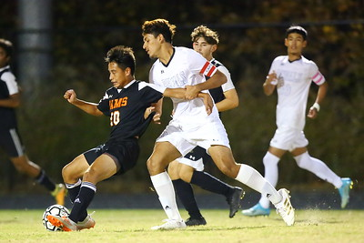 George P. Smith/The Montgomery Sentinel    Jefferson Perez (20), a freshman, who would score one of Rockville's goals, holds his own despite being manhandled by Blake captain Charly Naves (9).
