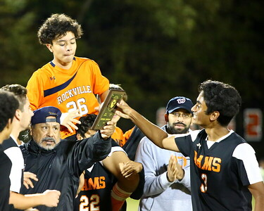 George P. Smith/The Montgomery Sentinel    Rockville coach Julio Zarate hands the 3A West Region II trophy to senior Madhav Pillai (3) as the Rockvile boys celebrate after defeating Blake 2-1 at home to capture the 3A West Region II title.