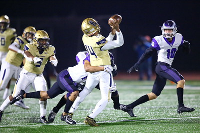 George P. Smith/The Montgomery Sentinel    Remarkably, Good Counsel quarterback Chase Williams (14) got the ball to Cole Heflin (11) despite being in the grasp of Gonzaga's Kye Holmes (1) and about to get sacked.