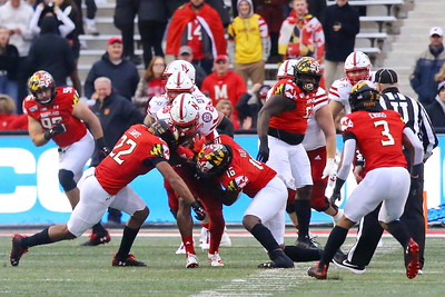 George P. Smith/The Montgomery Sentinel    Maryland's Isaiah Davis (22) and Ayinde Eley (16) apply a double whamy on Nebraska's Dedrick Mills (26).