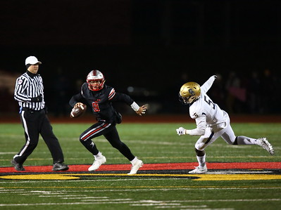 George P. Smith/The Montgomery Sentinel    St. John's Sol-Jay Maiava (9) rolls out of the pocket with Good Counsel's Caleb Dennis (5) giving chase during the WCAC Championship game played at Catholic University on Sunday, November 24, 2019.