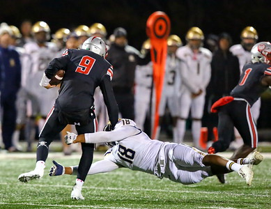 George P. Smith/The Montgomery Sentinel    Good Counsel's Kristopher Jenkins (18) makes a diving tackle on St. John's quarterback Sol-Jay Maiava (9) during the WCAC Championship game against St. Johns played at Catholic University on Sunday, November 24, 2019.