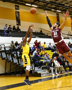 George P. Smith/The Montgomery Sentinel    Fairmont State's Kenzie Melko-Marshall (31) flies past trying to block the three by Bowie State's David Belle (11).