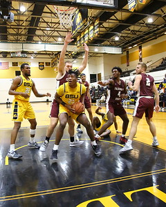 George P. Smith/The Montgomery Sentinel    Bowie State's Saiquan Jamison (21) pump fakes before going up with a rebound past Fairmont State's looming Seth Younkin (32).