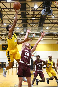 George P. Smith/The Montgomery Sentinel    Bowie State's Cameron Hayes (22) taking it to the hoop past Fairmont State's Jacob Brown (14).