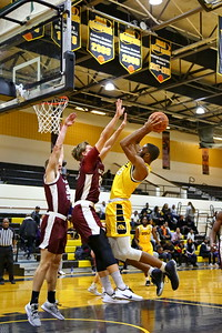 George P. Smith/The Montgomery Sentinel    Bowie State's Yolance Fleming (25) bends over backwards to get this shot off over Fairmont State's Przemyshlaw Golek (23) and Seth Younkin (32).