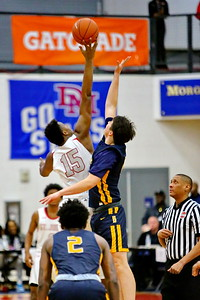 George P. Smith/The Montgomery Sentinel    St. John's Amani Hasberry (15) bests Bullis' William Moreau (11) at the tip off.