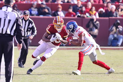 George P. Smith/The Montgomery Sentinel    Redskins' Kevin Harmon (13) puts a shoulder down as Giants' Sam Beal (23) comes over to drive him out of bounds.
