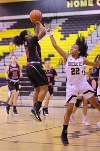 George P. Smith/The Montgomery Sentinel    Quince Orchard's Anaya Badmus (3) with the jumper in the paint over Richard Montgomery's Gloria Moudou (22).