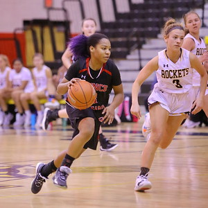 George P. Smith/The Montgomery Sentinel    Quince Orchard's Anaya Badmus (3) drives up court with Richard Montgomery's Una Mekic (3) in pursuit.