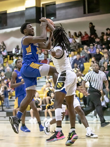 January 10, 2020 -Gaithersburg's Jao Ituka drives and draws a foul on Richard Montgomery's Henok Kassahun. Ituka, who faced foul trouble most of the game, brought Gaithersburg back from a double-digit defecit with 10 second-half points but they fell short 74-73 on January 10th. Photo by Mike Clark/The Montgomery Sentinel