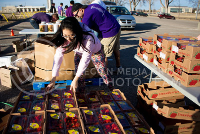Sarocha Pradyawong, PhD Graduate in Biological and Agriculture Engineering, picks up a box of strawberries to distribute at the Mobile Food Pantry sponsored by HandsOn K-State on Feb. 10. The Mobile Food Pantry is aimed at providing food securtiy for Riley County and K-State affliated residents. (Alanud Alanazi | The Collegian)