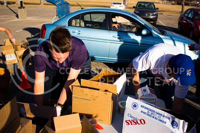 Nathan Shmidt, freshman in Finance, and Kaden Littrell, junior in Marketing, unpack boxes of diary products to distribute at the Mobile Food Pantry sponsored by HandsOn K-State on Feb. 10. The Mobile Food Pantry is aimed at providing food securtiy for Riley County and K-State affliated residents. (Alanud Alanazi | The Collegian)