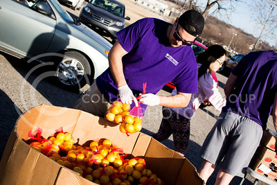Dominique Hoover, senior in Mechanical Engineering, picks up lemons to distribute at the Mobile Food Pantry sponsored by HandsOn K-State on Feb. 10. The Mobile Food Pantry is aimed at providing food securtiy for Riley County and K-State affliated residents. (Alanud Alanazi   The Collegian)