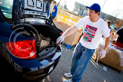Kaden Littrell, junior in Marketing, places a box of diary products in the trunk of the car at the Mobile Food Pantry sponsored by HandsOn K-State on Feb. 10. The Mobile Food Pantry is aimed at providing food securtiy for Riley County and K-State affliated residents, where residents can drive up to an open line of foods. (Alanud Alanazi | The Collegian)