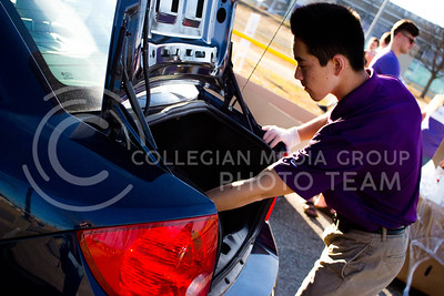 Jesses Chen, sophomore in Marketing, places a couple of bags of sweet potatos in the trunk of the car at the Mobile Food Pantry sponsored by HandsOn K-State on Feb. 10. The Mobile Food Pantry is aimed at providing food securtiy for Riley County and K-State affliated residents, where residents can drive up to an open line of foods. (Alanud Alanazi | The Collegian)