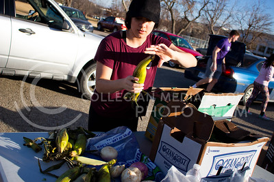 Chloe Nelson, junior in Leadership Studies and non-Profit Community Serivces, picks up corns to distribute to residents at the Mobile Food Pantry sponsored by HandsOn K-State on Feb. 10. The Mobile Food Pantry is aimed at providing food securtiy for Riley County and K-State affliated residents, where residents can drive up to an open line of foods. (Alanud Alanazi | The Collegian)