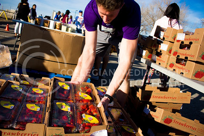 Cody Holthoas, junior in Business Management and Human Resources, picks up a box of strawberries at the Mobile Food Pantry sponsored by HandsOn K-State on Feb. 10. The Mobile Food Pantry is aimed at providing food securtiy for Riley County and K-State affliated residents. (Alanud Alanazi | The Collegian)